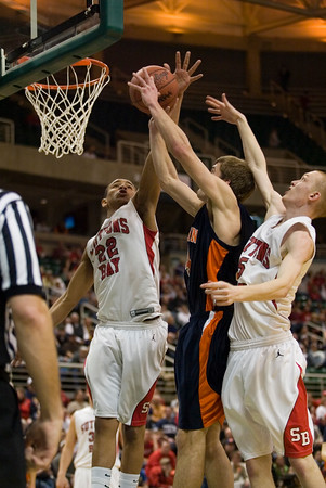Record-Eagle/Jan-Michael Stump<br /> Suttons Bay's Dwuan Anderson (22) blocks a shot by Bridgman's Parker Mojsienko (24) with help from David Wheelock (5) in the state semifinal game Thursday at the Breslin Center in East Lansing.