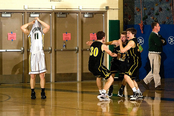 Record-Eagle/Jan-Michael Stump<br /> Traverse City Central's Dylan Roe (30) and Mack Sovereign (32) celebrate Erik Krueger's game-winning shot as Traverse City West's Luke Hessler (11) reacts to the buzzer-beating three-pointer.