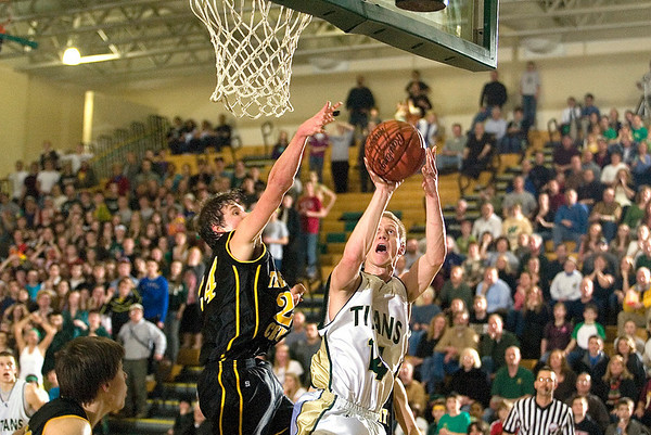 Record-Eagle/Jan-Michael Stump<br /> Traverse City West's Aaron Olsen (14) scores the tying basket over Traverse City Central's Ben Fischer (24) near the end of Friday's game.
