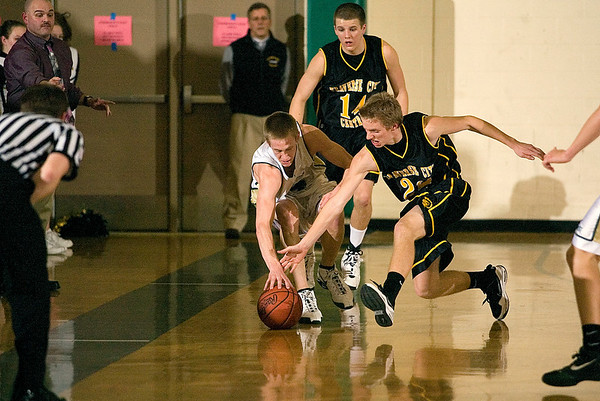 Record-Eagle/Jan-Michael Stump<br /> Traverse City Central's Erik Krueger (22) and Traverse City West's Aaron Olsen (14) chase down a loose ball in the second quarter of Friday's game.
