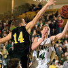 Record-Eagle/Jan-Michael Stump<br /> Traverse City West's Aaron Olsen (14) drives for a layup past Traverse City Central's Joe Prokes (14) in the third quarter of Friday's game.