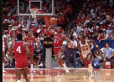 1983 FINAL FOUR:  Semi-Final Game, #34 NBA Hall of Famer Hakeem Olajuwon's team beat Louisville and then lost to Jim Valvano's North Carolina State team in an historic final...and the cameraman to the right of Hakeem sitting on the court filming the action in a blue sport shirt is Chuck Cohen, working for NCAA Productions.