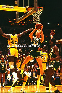 Celtics Larry Bird makes short bank shot vs James Worthy and Lakers during NBA Finals playoff game as #21 Michael Cooper and Celtics Cornbread Maxwell look on.