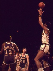 Kareem shoots as Keith Erickson and Wilt watch