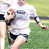 Will Fehlinger | The Herald-Tribune<br /> Liz Heidlage carries the pigskin for the junior class during this year's powder puff football game.