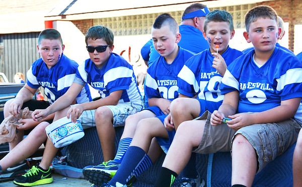 Christopher Aune | The Herald-Tribune<br /> Youth football players on a float enjoy lollipops as they pass them out.