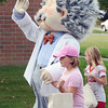 Will Fehlinger | The Herald-Tribune<br /> The George's Family Pharmacy mascot escorts a pair of youngsters at the homecoming parade Oct. 6.