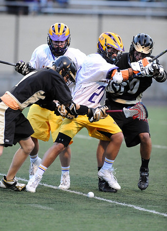 LACROSSE<br /> Monarch players Tyler Thorson, left, and Nathan Puldy, right, battle for the ball against Boulder's Billy Baumgartner, left, and Colin Termine, right.<br /> Photo by Marty Caivano/Camera/April 5, 2010