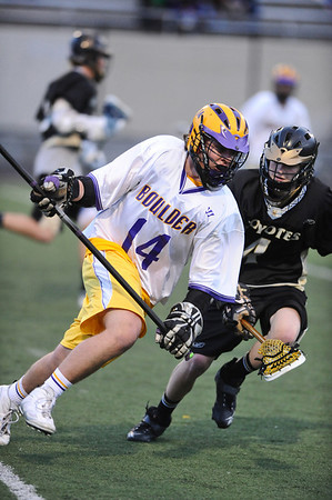 LACROSSE<br /> Boulder's Billy Baumgartner charges past Kyle Doner of Monarch.<br /> Photo by Marty Caivano/Camera/April 5, 2010
