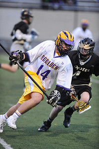 LACROSSE Boulder's Billy Baumgartner charges past Kyle Doner of Monarch. Photo by Marty Caivano/Camera/April 5, 2010