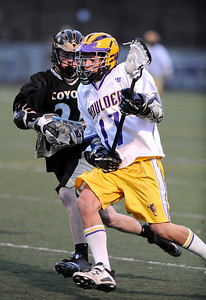 LACROSSE Boulder's Trevor Larson is pursued by Dylan Ritger of Monarch. Photo by Marty Caivano/Camera/April 5, 2010