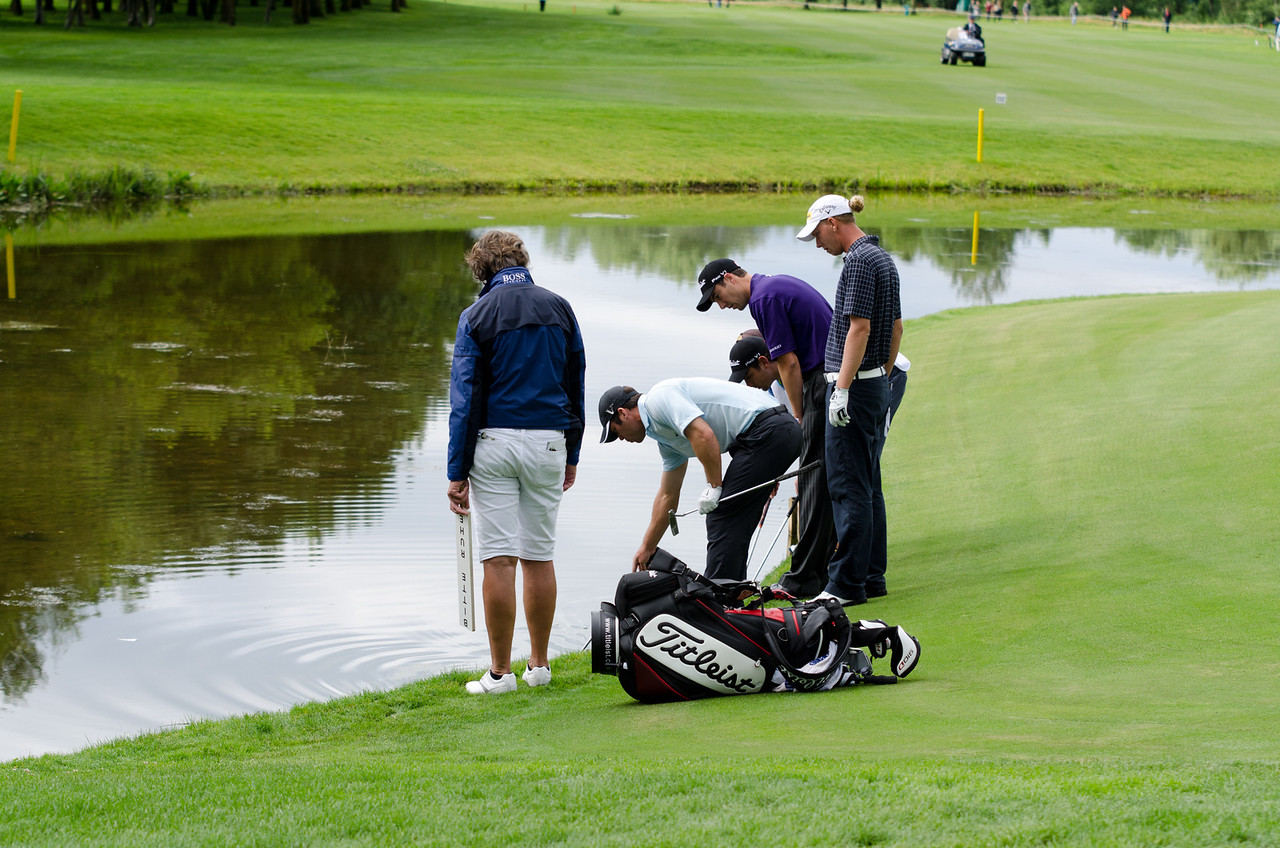 Marcel Siem's flight searching for his ball in the water hazard in front of green #11.