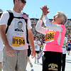 "Helen Kotris, of Denver, says a prayer next to a man, bib number not found on race list, at the finish line of the Bolder Boulder on Monday, May 28. For more photos of the race go to  <a href=""http://www.dailycamera.com"">http://www.dailycamera.com</a><br /> Jeremy Papasso/ Camera"