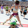 "Cailleach Way, of Centennial, leap frogs over Jencee Reardon, of Laramie, Wyo., at the finish line of the Bolder Boulder on Monday, May 28. For more photos of the race go to  <a href=""http://www.dailycamera.com"">http://www.dailycamera.com</a><br /> Jeremy Papasso/ Camera"
