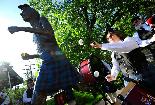 Gina McCutchon of the Centennial State Pipe and Drums plays beneath the Frank Shorter statue adorned with a kilt during the Citizen's Race of  the 2012 Bolder Boulder.<br /> Photo by Paul Aiken / The Camera