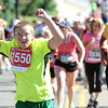 James Giglio of Littleton, Colorado acknowledges the cheers of the crowd during the Citizen's Race of  the 2012 Bolder Boulder.<br /> Photo by Paul Aiken / The Camera
