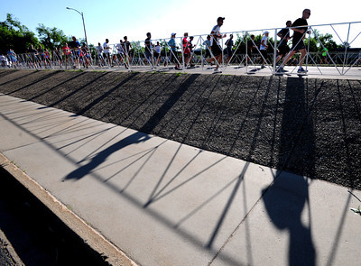 Runners cast a shadow as they run up Folsom to the stadium. For more photos and videos of the 34th Bolder Boulder, go to www.dailycamera.com. Cliff Grassmick / May 28, 2012