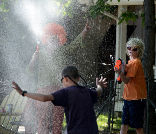 """Darrell Ansted, left, and Wes Golliher,  provides water to cool off the runners on Walnut Street.<br /> For more photos and videos of the 34th Bolder Boulder, go to  <a href=""""http://www.dailycamera.com"""">http://www.dailycamera.com</a>.<br /> Cliff Grassmick / May 28, 2012"""