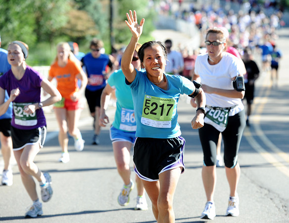 Xiubo Xu of Loveland, Colorado waves to family as she nears the finish line of the Citizen's Race of  the 2012 Bolder Boulder.<br /> Photo by Paul Aiken / The Camera