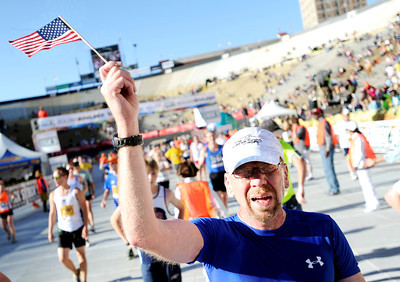 Bill Tongue, of Colorado Springs, holds an American flag after crossing the finish line inside Folsom Field on the University of Colorado campus on Monday, May 28, during the Bolder Boulder citizens race in Boulder, Colo. For more photos of the race go to www.dailycamera.com Jeremy Papasso/ Camera