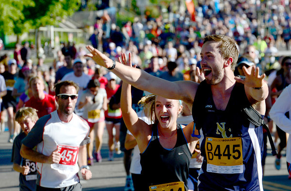 Janelle Kramer (left) and Michael Van Portfliet (right) give props to a band while running in the 2012 Bolder Boulder in Boulder, Colorado May 28, 2012. CAMERA/MARK LEFFINGWELL