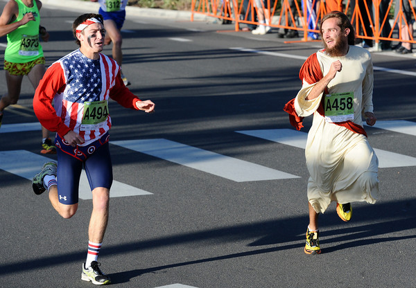 Chris Davis, dressed in his regular Bolder Boulder religious dress takes a look over a more patriotically dressed Grant Caswell as they take a brief lead at the start of the Citizen's Race during the  2012 Bolder Boulder.<br /> Photo by Paul Aiken / The Camera