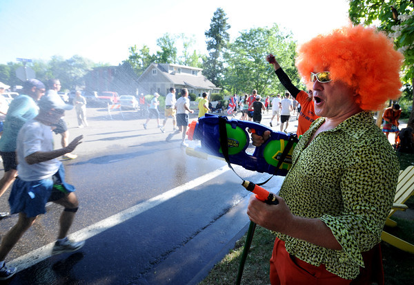 "Darrell Ansted provides water to cool off the runners on Walnut Street.<br /> For more photos and videos of the 34th Bolder Boulder, go to  <a href=""http://www.dailycamera.com"">http://www.dailycamera.com</a>.<br /> Cliff Grassmick / May 28, 2012"
