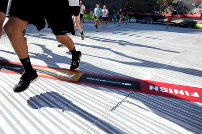 Racers and their shadows cross the finish line inside Folsom Field on the University of Colorado campus on Monday, May 28, during the Bolder Boulder race in Boulder, Colo. For more photos of the race go to www.dailycamera.com Jeremy Papasso/ Camera