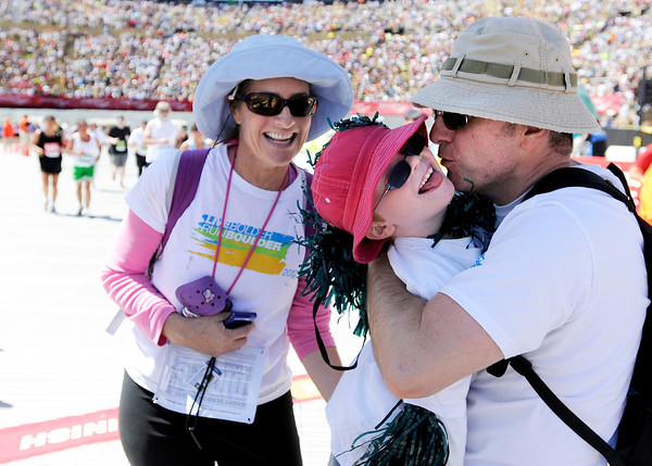 """Bulend Corbacioglu, of Boulder, kisses Aidan Corbacioglu at the finish line of the Bolder Boulder while Sonja Seitamo-Corbaci, also of Boulder, smiles in the background on Monday, May 28. For more photos of the race go to  <a href=""""http://www.dailycamera.com"""">http://www.dailycamera.com</a><br /> Jeremy Papasso/ Camera"""