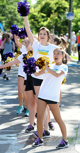 Frannie Yee, front, and Nora O'Neill of the Boulder High Poms cheer on the runner during the Citizen's Race of  the 2012 Bolder Boulder. Photo by Paul Aiken / The Camera