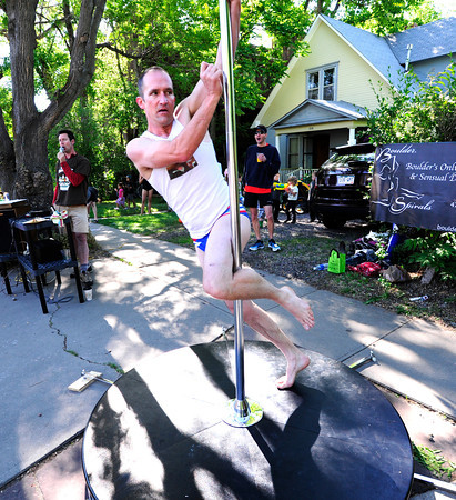 Erik Paulsrud takes a spin on the exercise pole during the Citizen's Race of  the 2012 Bolder Boulder.<br /> Photo by Paul Aiken / The Camera