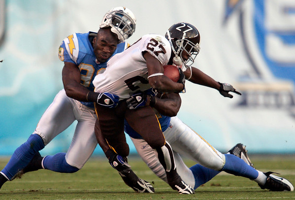 Denver Broncos running back Knowshon Moreno is dragged down by San Diego Chargers linebacker Kevin Burnett while gaining three-yards during the first quarter of an NFL football game Monday, Oct. 19, 2009 in San Diego. (AP Photo/Chris Park)