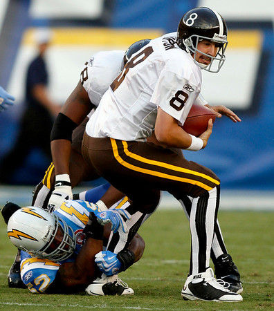 Denver Broncos quarterback Kyle Orton is dragged for a sack by San Diego Chargers defensive end Larry English for a two-yard loss during the first quarter of an NFL football game Monday, Oct. 19, 2009 in San Diego. (AP Photo/Denis Poroy)