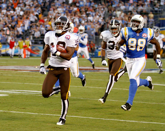 Denver Broncos kick returner Eddie Royal out runs San Diego Chargers' Kris Wilson while returning a kickoff 93-yards for a touchdown during the first quarter of the NFL football game Monday, Oct. 19, 2009 in San Diego. (AP Photo/Denis Poroy)