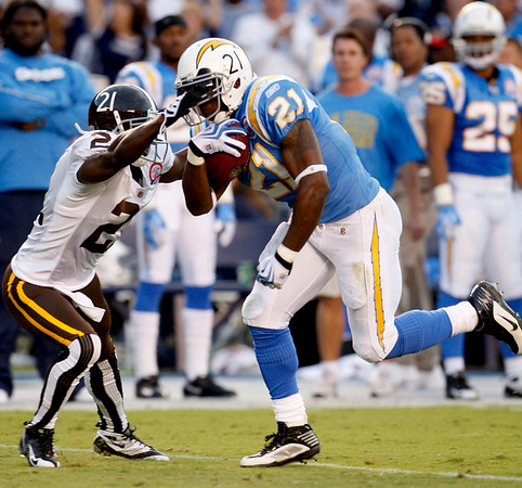 San Diego Chargers running back LaDainian Tomlinson has his face mask grabbed by Denver Broncos cornerback Andre' Goodman while gaining 25-yards on a pass during the first quarter of the NFL football game Monday, Oct. 19, 2009 in San Diego. (AP Photo/Lenny Ignelzi)