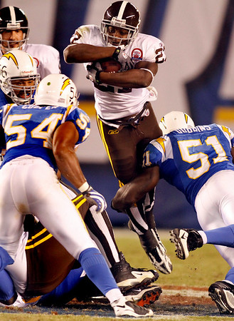 Denver Broncos running back Knowshon Moreno, center, goes over the top of San Diego Chargers linebackers Tim Dobbins (51) and Stephen Cooper (54) while gaining two yards for a first down in the third quarter of the NFL football game Monday, Oct. 19, 2009 in San Diego.  (AP Photo/Denis Poroy)