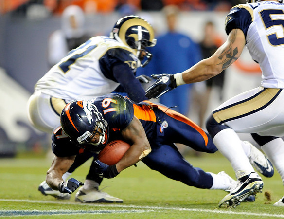 Denver Broncos wide receiver Eddie Royal (19) scores a touchdown against St. Louis Rams safety Oshiomogho Atogwe (21) and James Laurinaitis (55) during the second half of an NFL football game Sunday, Nov. 28, 2010, in Denver. (AP Photo/Chris Schneider)
