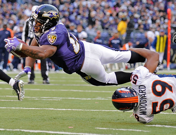Baltimore Ravens running back Ray Rice, top, leaps into the end zone for a touchdown as Denver Broncos linebacker Wesley Woodyard (59) tries to hang on  during the fourth quarter of an NFL football game, Sunday, Nov. 1, 2009, in Baltimore. The Ravens won 30-7. (AP Photo/Nick Wass)