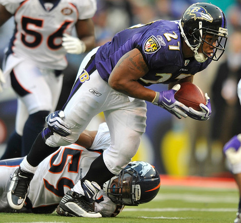Baltimore Ravens running back Ray Rice (27) leaps into the end zone for a touchdown as Denver Broncos linebacker Wesley Woodyard, bottom, tries to hang  on during the fourth quarter of an NFL football game, Sunday, Nov. 1, 2009, in Baltimore. The Ravens won 30-7. (AP Photo/Gail Burton)