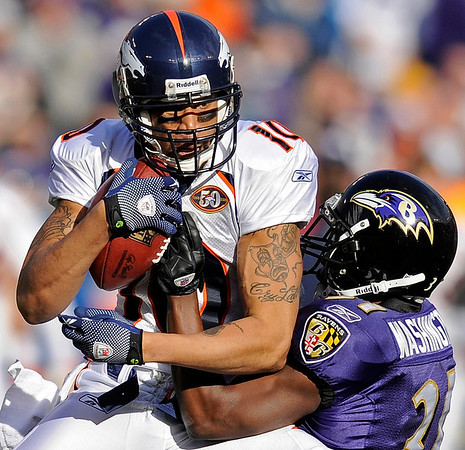 Denver Broncos wide receiver Jabar Gaffney, left, is stopped by Baltimore Ravens cornerback Fabian Washington during the third quarter of an NFL football game, Sunday, Nov. 1, 2009, in Baltimore. (AP Photo/Nick Wass)