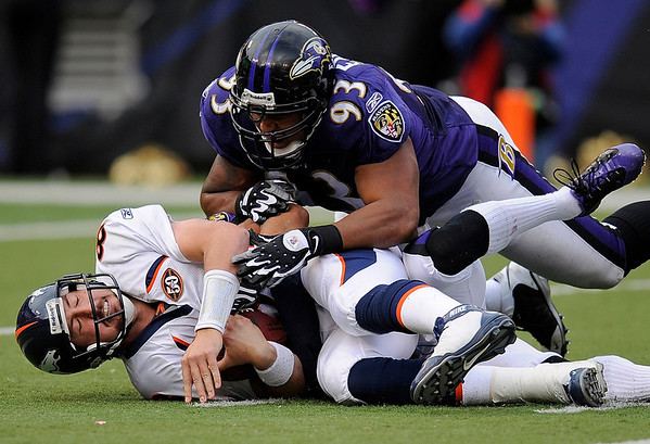 Denver Broncos quarterback Kyle Orton, left, lies on the field after being sacked in the fourth quarter by Baltimore Ravens cornerback Chris Carr (partially obscured) and defensive tackle Dwan Edwards, top, during an NFL football game, Sunday, Nov. 1, 2009, in Baltimore. Baltimore won the game 30-7. (AP Photo/Nick Wass)