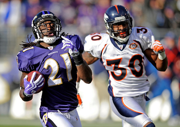 Baltimore Ravens cornerback Lardarius Webb, left, carries the ball for a touchdown as Denver Broncos safety David Bruton pursues during the third quarter of an NFL football game, Sunday, Nov. 1, 2009, in Baltimore. (AP Photo/Nick Wass)