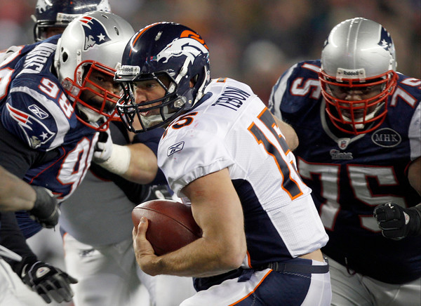 Denver Broncos quarterback Tim Tebow (15) tries to avoid a being tackled by New England Patriots defensive tackle Gerard Warren (98) and Vince Wilfork (75) during the second half of an NFL divisional playoff football game Saturday, Jan. 14, 2012, in Foxborough, Mass. (AP Photo/Charles Krupa)