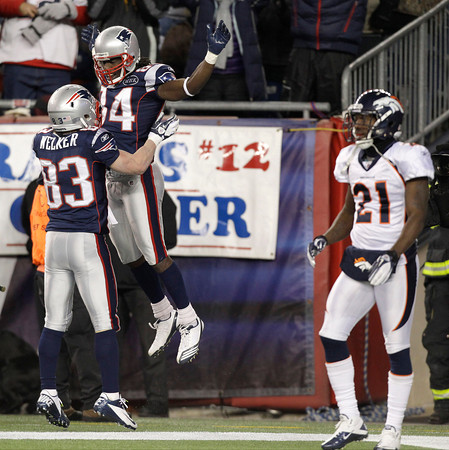 Denver Broncos cornerback Andre' Goodman (21) walks past New England Patriots wide receiver Deion Branch (84) as he celebrates his 61-yard touchdown pass reception with Wes Welker (83) during the first half of an NFL divisional playoff football game Saturday, Jan. 14, 2012, in Foxborough, Mass. (AP Photo/Stephan Savoia)