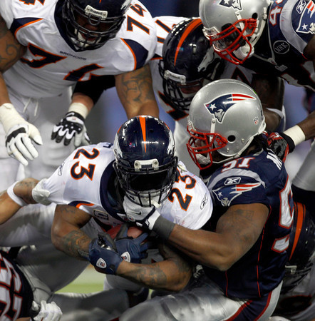 Denver Broncos running back Willis McGahee (23) is tackled by New England Patriots middle linebacker Jerod Mayo (51) as he scores on a five yard run during the first half of an NFL divisional playoff football game Saturday, Jan. 14, 2012, in Foxborough, Mass. (AP Photo/Charles Krupa)