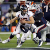 Denver Broncos quarterback Tim Tebow (15) scrambles to avoid a tackle by New England Patriots defensive end Shaun Ellis (94) during the second half of an NFL divisional playoff football game Saturday, Jan. 14, 2012, in Foxborough, Mass. (AP Photo/Charles Krupa)