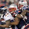 Denver Broncos running back Willis McGahee (23) is tackled by New England Patriots middle linebacker Jerod Mayo (51) and James Ihedigbo, right,  during the first half of an NFL divisional playoff football game Saturday, Jan. 14, 2012, in Foxborough, Mass. (AP Photo/Elise Amendola)