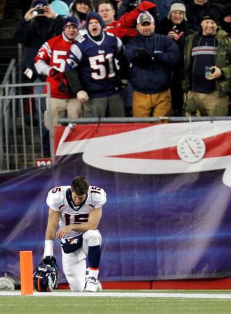 Denver Broncos quarterback Tim Tebow kneels in the end zone before  an NFL divisional playoff football game against the New England Patriots Saturday, Jan. 14, 2012, in Foxborough, Mass. (AP Photo/Elise Amendola)