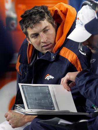 Denver Broncos quarterback Tim Tebow examines game photos on the team bench during the second half of an NFL divisional playoff football game against the New England Patriots Saturday, Jan. 14, 2012, in Foxborough, Mass. (AP Photo/Charles Krupa)