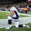 Denver Broncos quarterback Tim Tebow kneels on the sidelines before an NFL divisional playoff football game against the New England Patriots Saturday, Jan. 14, 2012, in Foxborough, Mass. (AP Photo/Stephan Savoia)